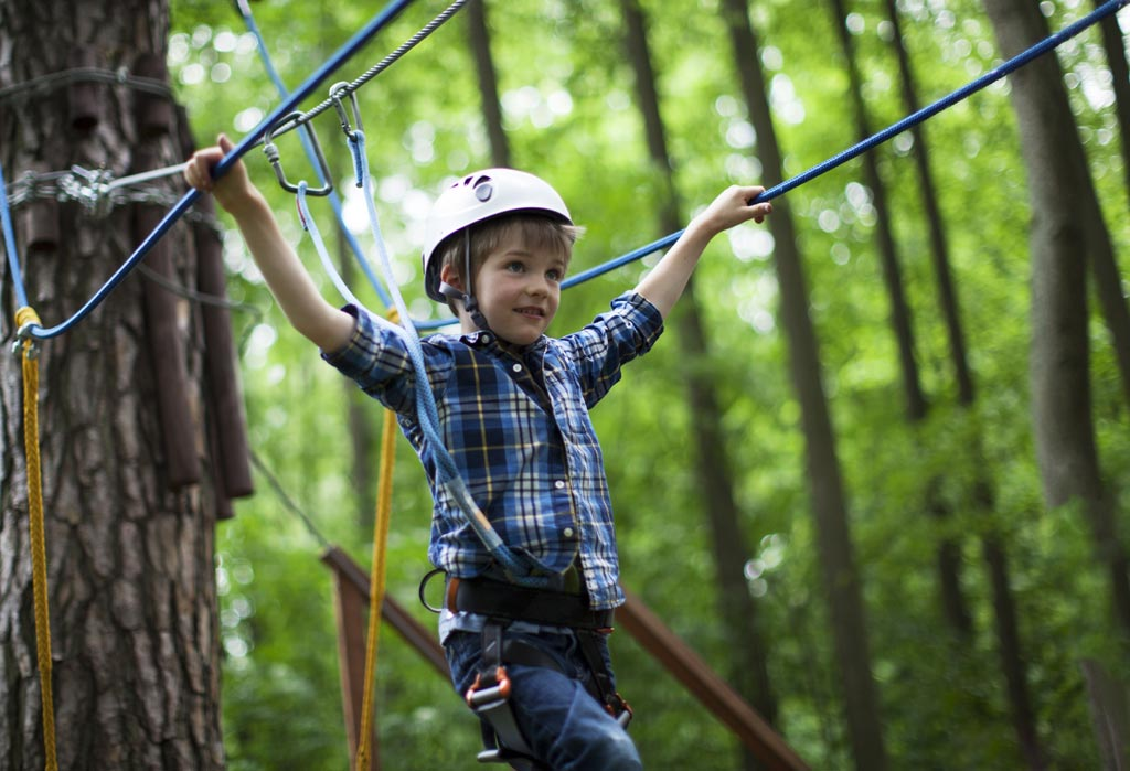 Enfant sur le pont de singe du parcours enfant